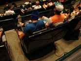 Brazilians strapped to moving chair (3-D cinema showing awful dinosaur movie)