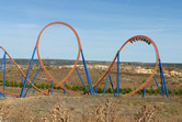 Huge looping roller coaster stretching beyond the park's borders
